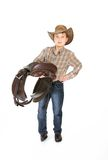 Young boy carrying a saddle Royalty Free Stock Photo