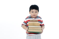 Young boy carrying a stack of books Royalty Free Stock Photography