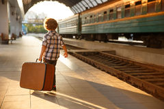 Young boy carrying suitcase in railway station. Back view of young blonde boy carrying brown suitcase standing on railway platform with train on background royalty free stock image
