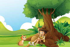 A young boy and a cat under the big tree Royalty Free Stock Image