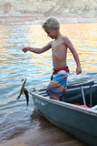 Young Boy Catches a Fish. A young boy holds up two fish that he caught at the lake Stock Photography