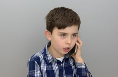 Young boy on cell phone. Close up portrait of child speaking on smart phone. Shot taken with grey background stock photography