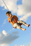 Young boy on chain swing. Having fun in the evening sun against lovely blue sky Stock Images