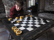 Young Boy Checkers - Wakulla Lodge. A young10 year-old boy concentrates on his next move during a checker game before dinner at the 1930's Wakulla Springs Lodge Stock Photos