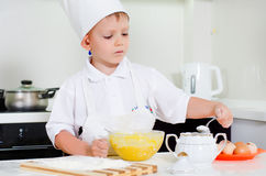 Young boy chef adding ingredients to his bowl Royalty Free Stock Image
