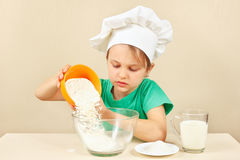 Young boy in chefs hat pours flour for baking cake Stock Images