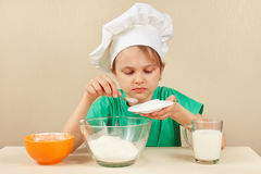 Young boy in chefs hat pours sugar for baking cake Stock Photography