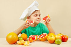 Young boy in chefs hat with two slices of grapefruit at table with fruits Stock Image