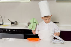 Young boy in chefs uniform washing the dishes Stock Photos
