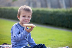 A young boy child eating a slice of pizza Royalty Free Stock Photos