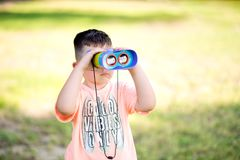 Young boy child playing pretend explorer adventure safari game outdoors with binoculars. Summer green background Royalty Free Stock Image