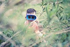 Young boy child playing pretend explorer adventure safari game outdoors with binoculars. Summer green background Stock Photos