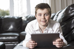 Young boy child resting on his hands laying down  a sofa using tablet computer. A young boy child resting on his hands laying down on a sofa using tablet Royalty Free Stock Images