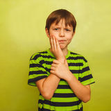 Young boy child toothache pain in mouth, dental. Pain, holding his cheek on a green background royalty free stock image