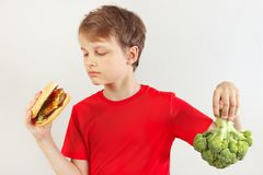 Young boy chooses between fastfood and vegetable on white background. Young boy chooses between fastfood and vegetable on a white background stock photography
