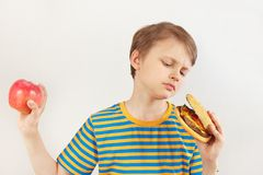 Young boy chooses between hamburger and apple on white background stock photography