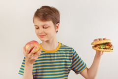 Young boy chooses between hamburger and healthy diet on white background royalty free stock photos