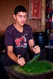 young boy chopping coriander with a round knife on a wooden board royalty free stock images