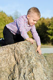 Young boy clambering on rocks Royalty Free Stock Photography