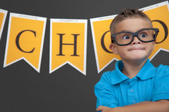 Young Boy in the Classroom. A young nerd boy smiles for the camera in classroom royalty free stock images