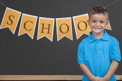 Young Boy in the Classroom. A young smiles for the camera in a classroom stock photography