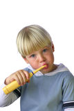 Young boy cleaning his teeth. An isolated picture of a young boy cleaning his teeth stock photography