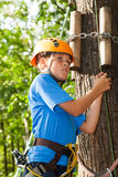 Boy with climber equipment intently keeps rope Stock Image