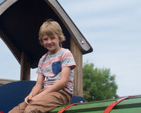 Young boy on climbing frame. Younf male caucasian child on play equipment in playground royalty free stock images