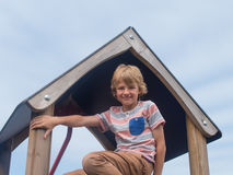 Young boy on climbing frame. Younf male caucasian child on play equipment in playground royalty free stock image
