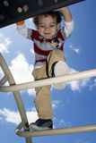 Young Boy Climbing on Jungle Gym. With the blue  sky in the background Royalty Free Stock Photography