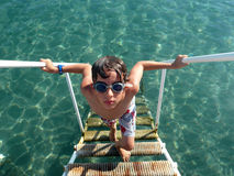 Young boy climbing the ladder in sea Stock Photo