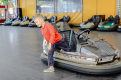 Young boy climbing out of a bumper car Stock Photography