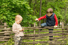 Young boy climbing over a rustic wooden fence Royalty Free Stock Photography