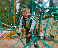 Young Boy Climbing Playground Structure. Child laughing as climbs spiderweb play structure. Date 2012 Stock Photo