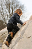Young boy climbing rock Stock Images