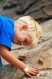 Young boy climbing rocks stock photos