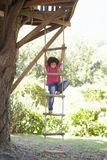 Young Boy Climbing Rope Ladder To Treehouse Stock Photography