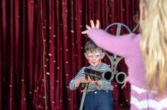 Young Boy Clown Aiming Large Gun at Blond Girl Stock Photo