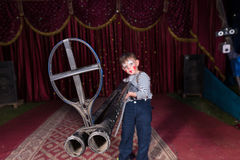 Young Boy Clown Holding Large Gun on Stage Royalty Free Stock Photography