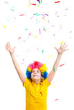 The young boy in clown wig throws colored confetti Stock Images