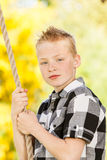 Young boy clutching a rope outdoors in the garden Stock Photos