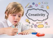 Young boy coloring with Creativity text with drawings graphics royalty free stock photos