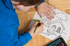 Young Boy Coloring on Floor Royalty Free Stock Images