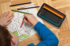 Young Boy Coloring on Floor Royalty Free Stock Photos