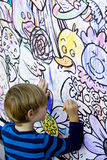 Young boy coloring a wall. A young child coloring on a big wall Royalty Free Stock Image