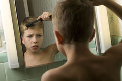 Young Boy Combing His Hair Royalty Free Stock Photos
