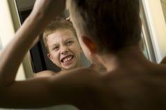 Young Boy Combing His Hair stock photos