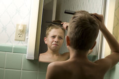 Young Boy Combing His Hair Royalty Free Stock Photo