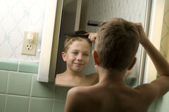 Young Boy Combing His Hair Stock Image