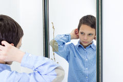 Young Boy Combing His Hair in Mirror Stock Photography
